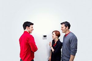 Homeowners Discussing Thermostat with Technician